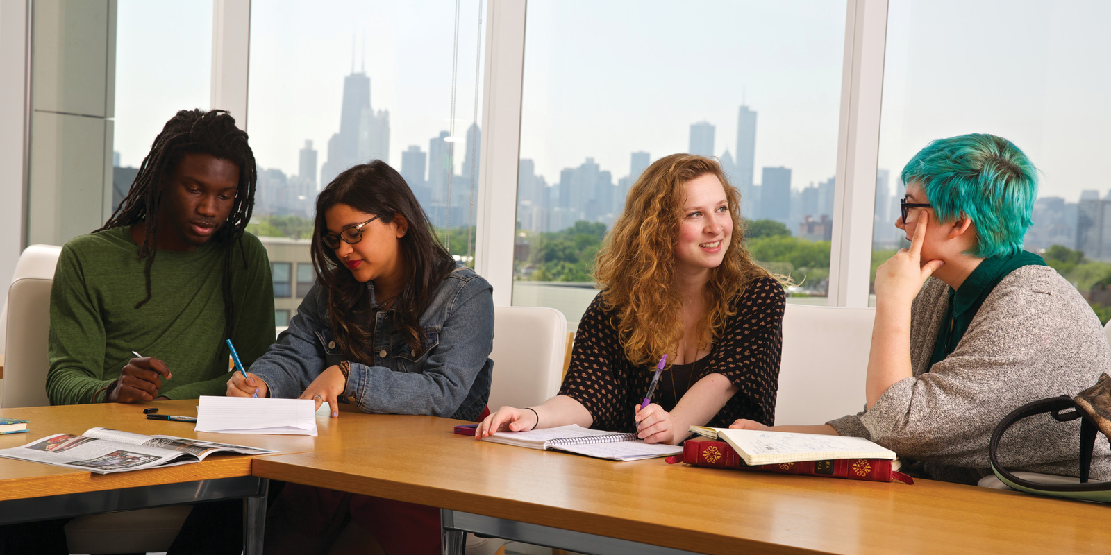 Students reviewing class notes behind the Chicago skyline.