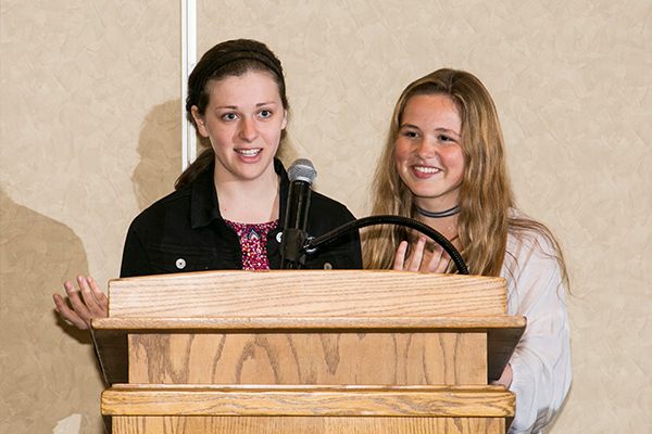 Two women speaking at a podium