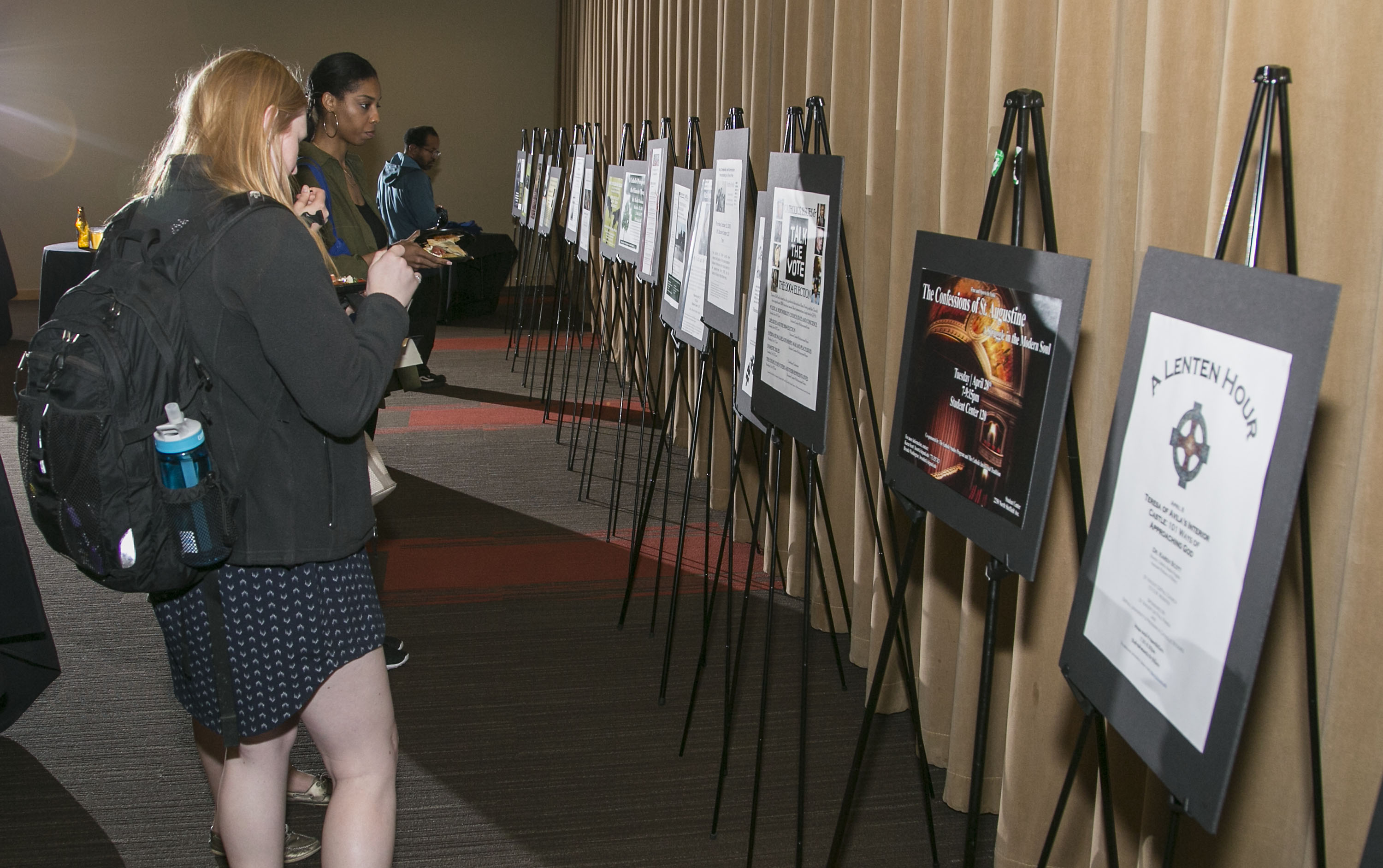 Guests admire posters of past Catholic Studies events