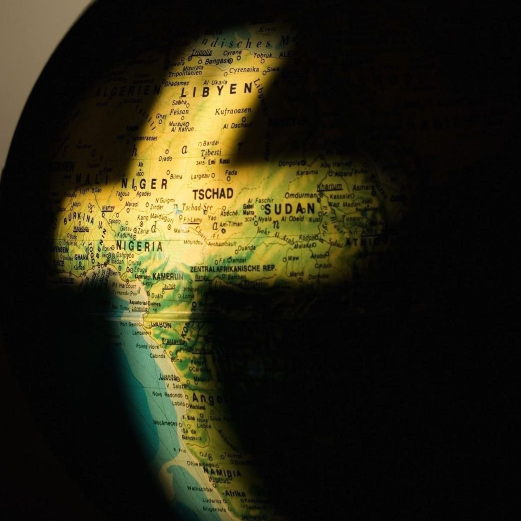 Globe with light shining on Africa in the shape of a cross