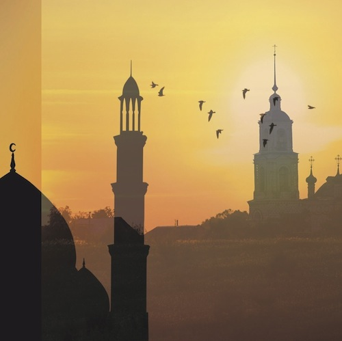 Silhouettes of a mosque and church side by side at sunset
