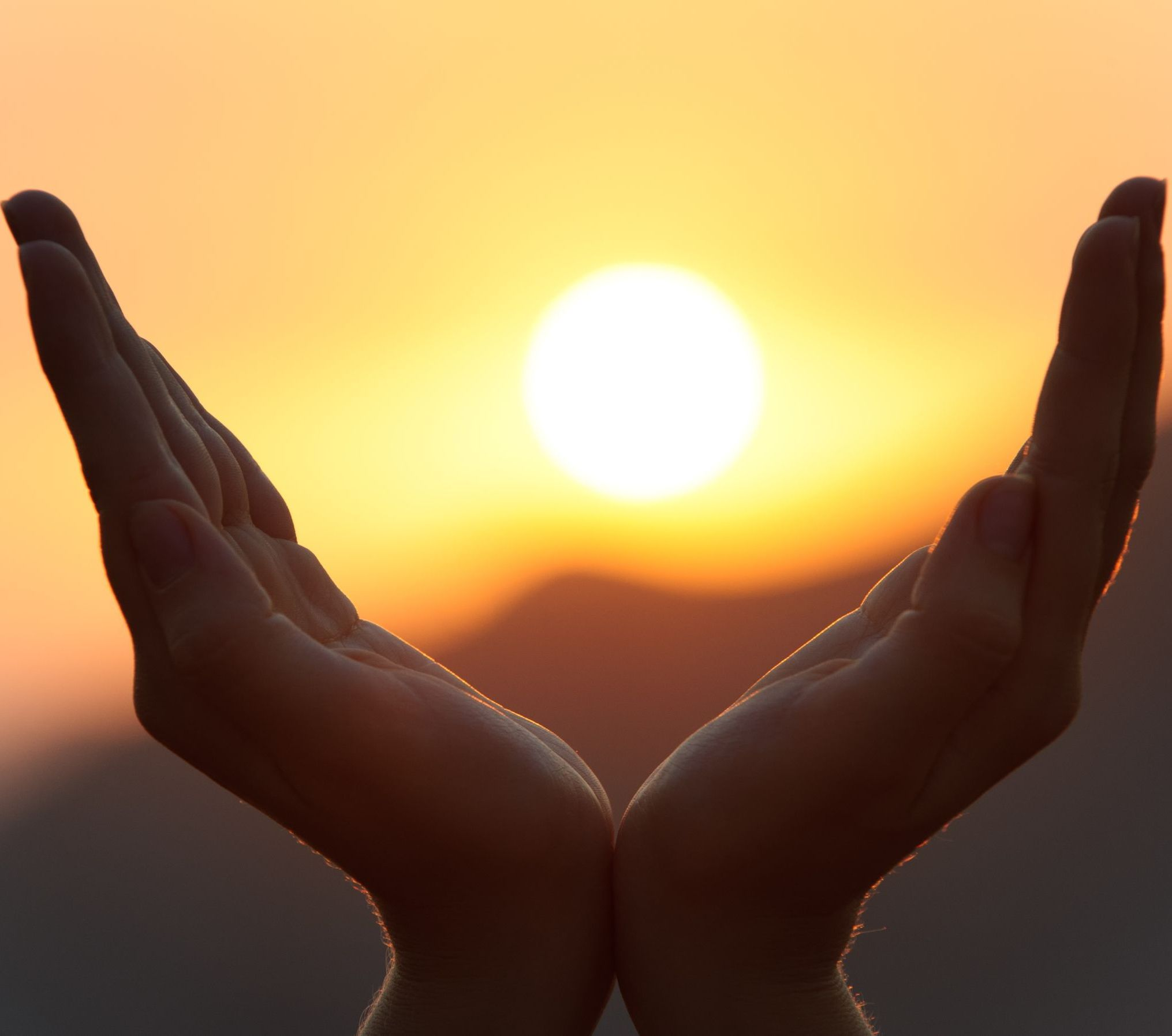 Close-up image of open hands with a sunrise/sunset in the background