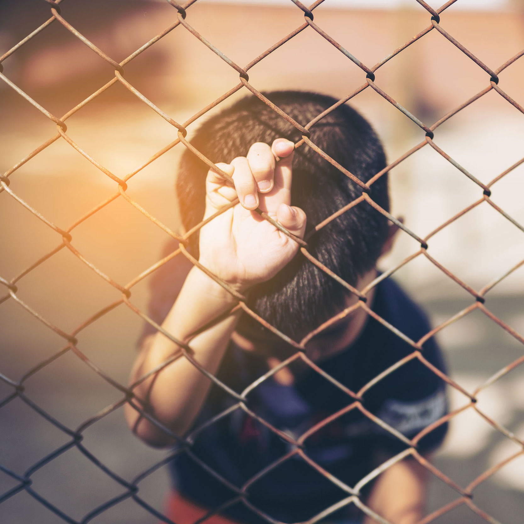 Child alone behind a fence