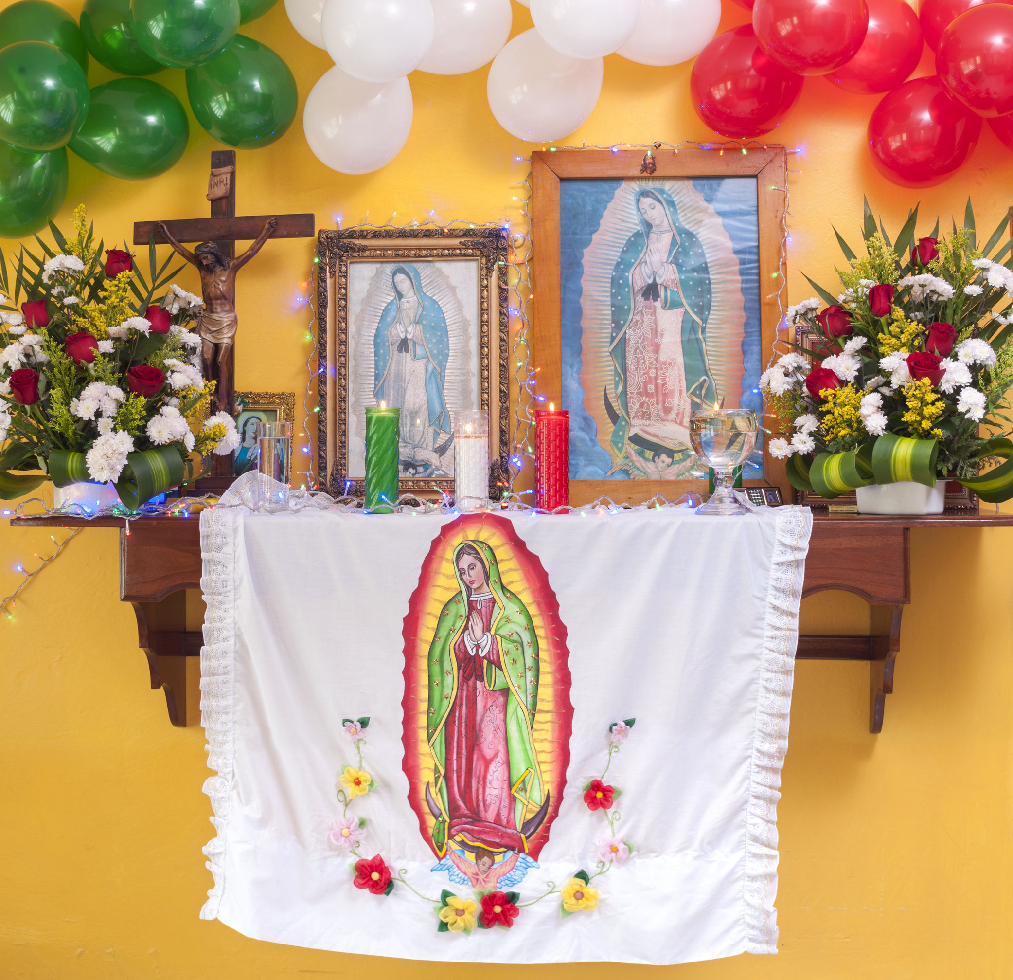 An altar for Our Lady of Guadalupe with pictures, candles, flowers