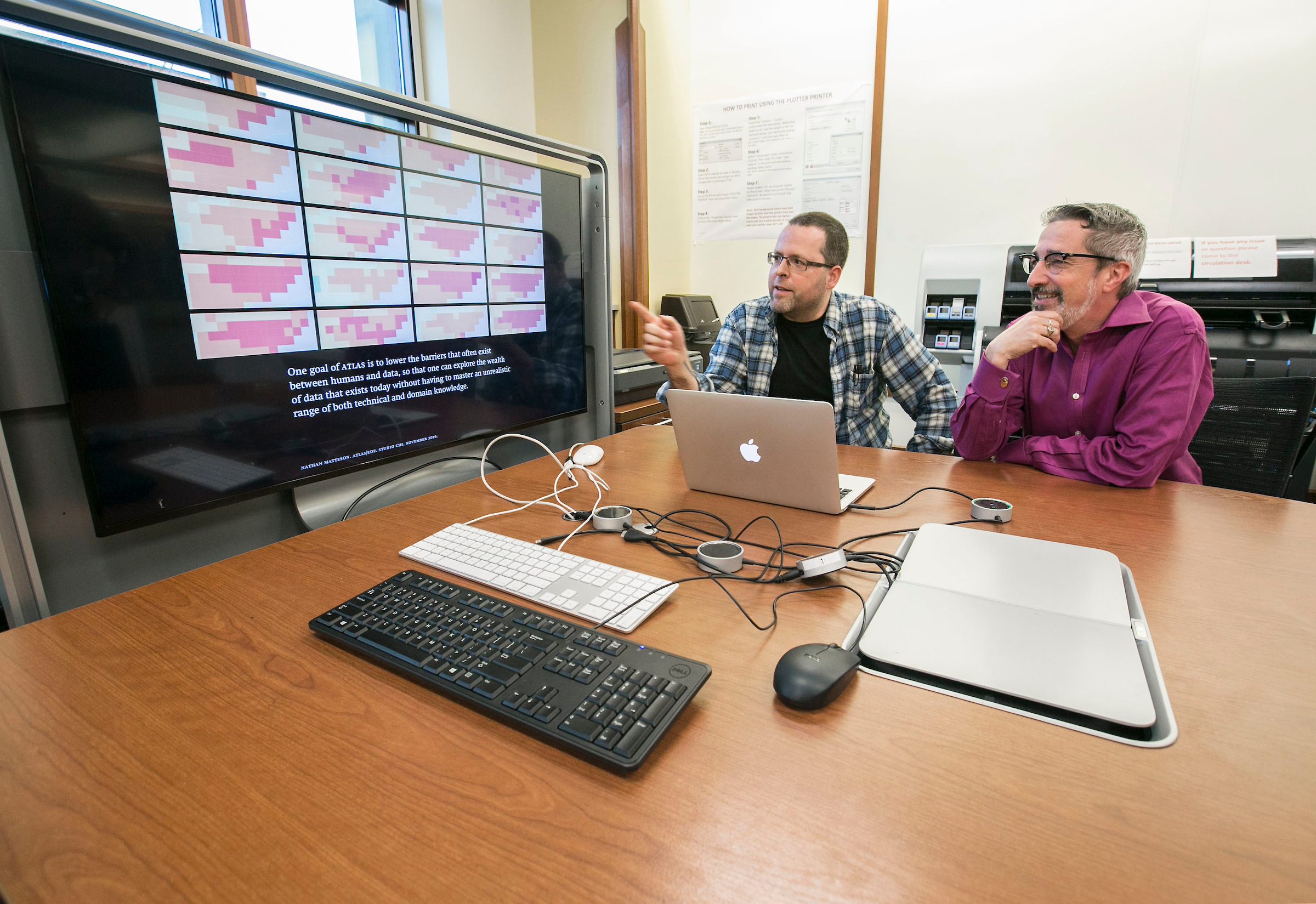 Nathan Matteson, left, assistant professor in the College of Computing and Digital Media, and Paul Jaskot, director of Studio χ (CHI: Computing/Humanities Interface) look over a project during an open house